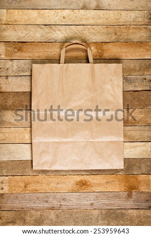 Paper bag on a wooden texture - stock photo