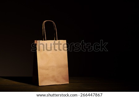 Paper bag on old wooden background for natural recycle concept packshot - stock photo