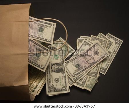 Paper bag with cash/Money Bag/Cash spilling out a paper bag - stock photo