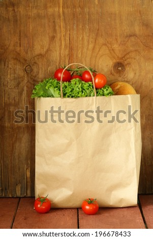 paper bag with food, lettuce, tomatoes, bread on a wooden background - stock photo