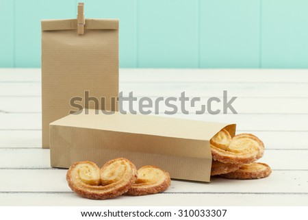 Paper bags with puff pastry heart cookies on a white wooden table. A turquoise wainscot in the background. - stock photo