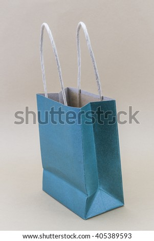 Paper blue shopping bag isolated on brown background - stock photo