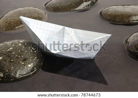 Paper boat floating in calm black water background - stock photo