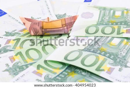 Paper boat floating over hundred euro bills - stock photo