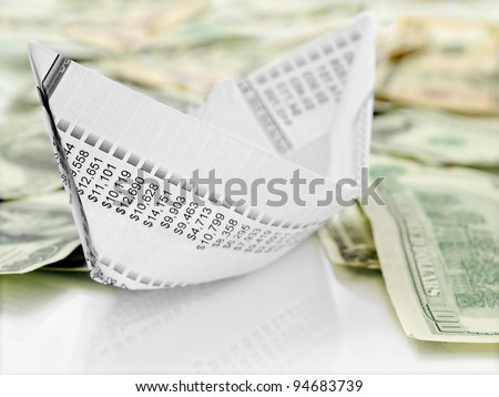 Paper Boat. Origami  paper boat made from financial  document on money background - stock photo