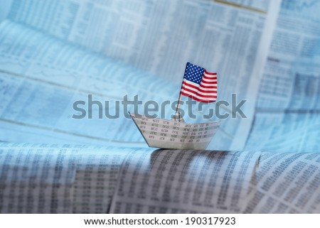 Paper boat with US flag shipping on financial news. - stock photo