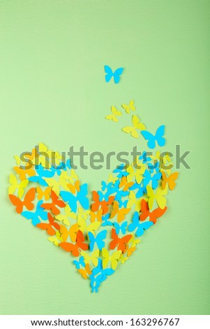 Paper butterflies on green wall - stock photo