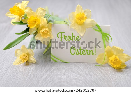 """Paper card with greeting """"Happy Easter"""" in German language and narcissus flowers - stock photo"""