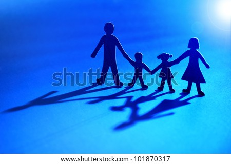 Paper chain family standing holding hands looking towards the light concept for family protection or religion - moving into the light - stock photo