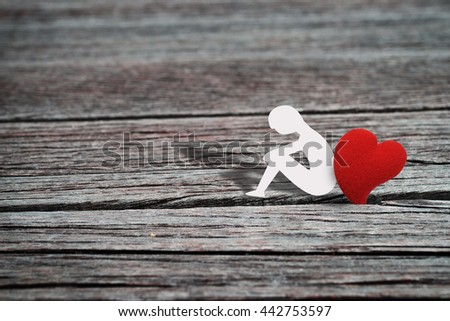 Paper character of man sitting alone with one heart shape ,grunge wood background. Abstract love background in lonely love concept for Valentine's day season. Vintage style. - stock photo