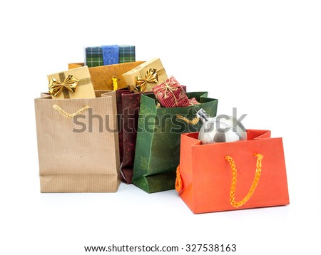 Paper christmas shopping bags with christmas presents and silver christmas ball shot on white background - stock photo