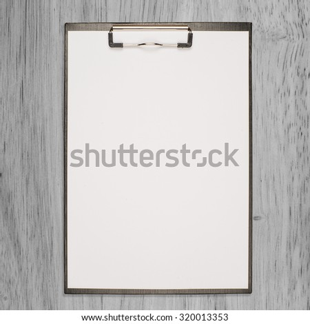 paper clipboard on wood background and texture - stock photo