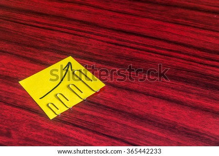 Paper clips attached by size on a yellow note with an arrow written on it. - stock photo