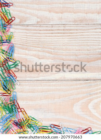 Paper clips in a random pattern on two sides of the image. A whitewashed wood background with multi colored paper clips. - stock photo