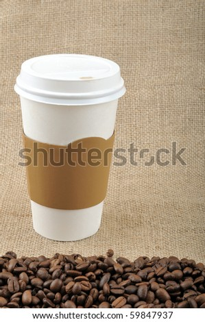Paper coffee cup with safety cardboard collar on jute background with coffee beans and copy space. - stock photo