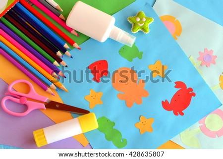 Paper colored sea animals and flowers, paper applique cards. Summer craft idea. Children creativity. Application simple. Glue, scissors, a set of pencils, eraser. Children background  - stock photo