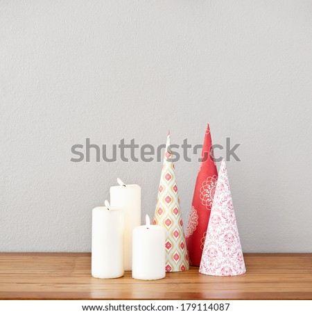 Paper cones and lit candles on a side board as deco - stock photo