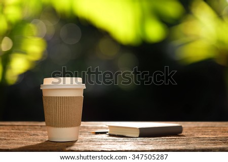 Paper cup of coffee and book in the garden - stock photo