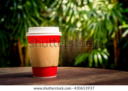 Paper cup of coffee in the garden - stock photo