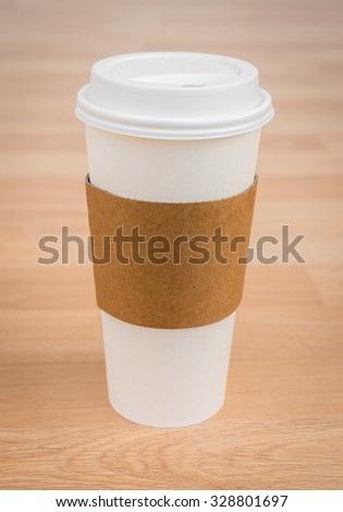 Paper cup of coffee on wood background - stock photo