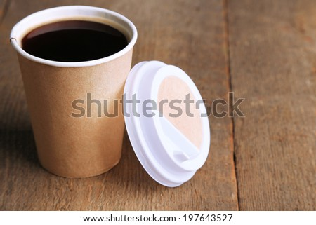 Paper cup of coffee on wooden table - stock photo
