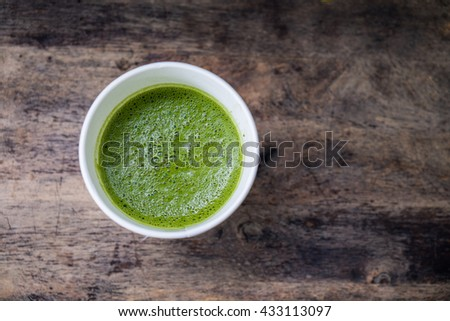Paper cup of matcha green tea on table background, selective focus. - stock photo