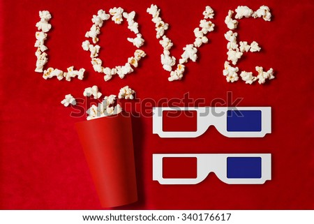 paper cup with popcorn and 3D glasses lined word on red background. mock up. top view. - stock photo