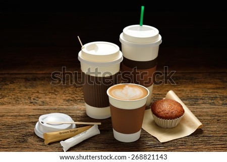 Paper cups of coffee latte and cake on wooden background - stock photo