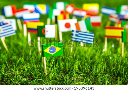Paper cut of flags on grass for championship  - stock photo