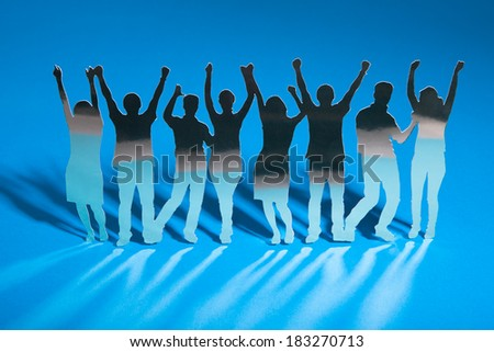 Paper Cut Out Of People Standing In A Line Over Blue Background - stock photo