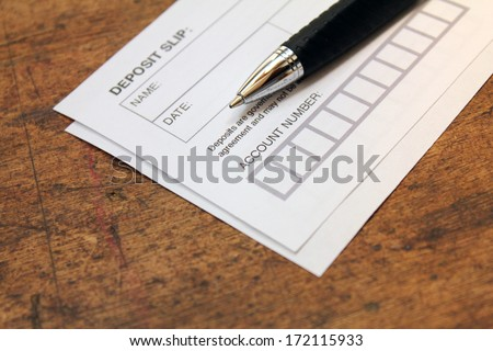 paper deposit slip and pen over wood background - stock photo