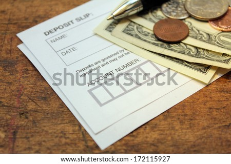 paper deposit slip, spare change and pen over wood background - stock photo