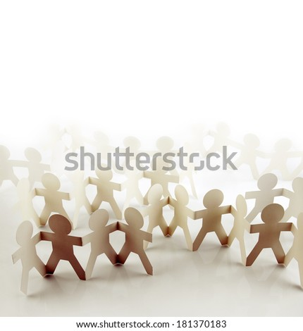 Paper doll team holding hands - stock photo