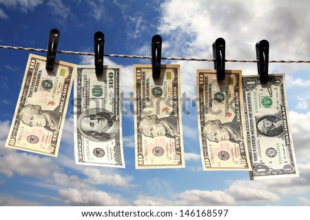 paper dollars are drying on rope under blue sky - stock photo