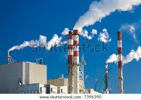 Paper factory with main chimneys expelling smoke into a deep blue sky - horizontal orientation - stock photo