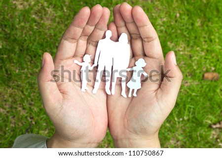 Paper family in hands on green grass background - stock photo