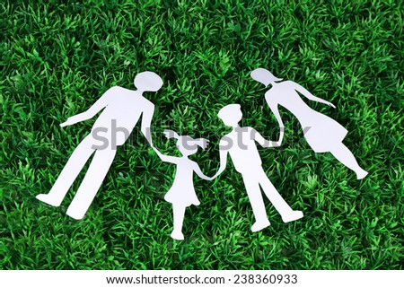 Paper family lying on green grass background - stock photo