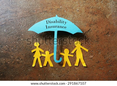 Paper family of four under a paper Disability Insurance umbrella                                - stock photo