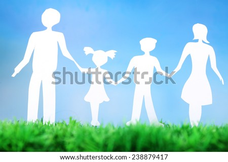 Paper family on green grass on light background - stock photo