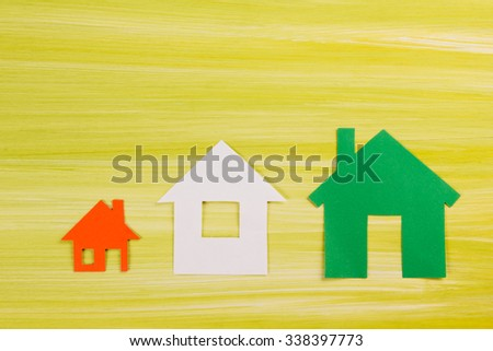 Paper house figure on green wooden background. Comparing houses. Eco house Green housing. Real Estate Concept. Top view. - stock photo