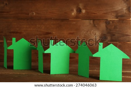 Paper houses on wooden background - stock photo