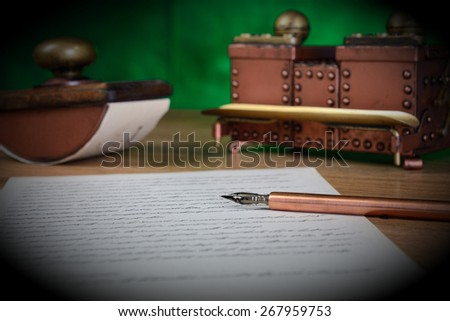 Paper, ink pen, inkstand and paperweight on the table. Low depth of field. - stock photo