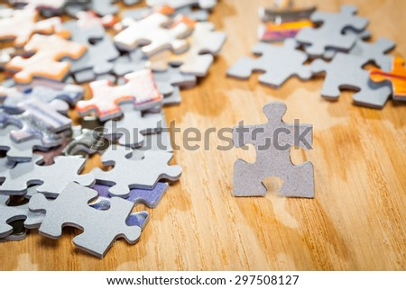 Paper jigsaw puzzle by pieces  on a table. Shallow depth of field - stock photo
