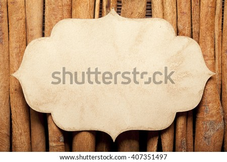 Paper label and cinnamon sticks on wooden wall background - stock photo