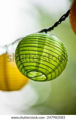 Paper lanterns hanging in the trees in summer at a party - stock photo