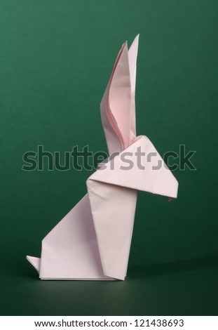 Paper made pink rabbit. 3D folded origami style. - stock photo