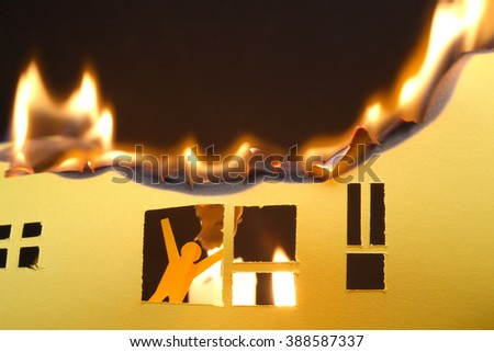 Paper man in window of burning house on dark background - stock photo
