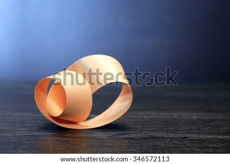 Paper Mobius strip on wooden board against dark background - stock photo