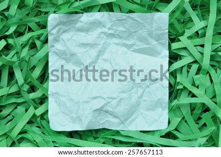 Paper note on green shredded paper - stock photo