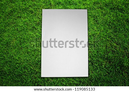 Paper on green grass field - stock photo